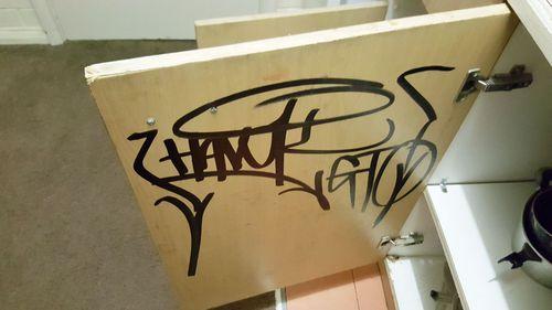 Graffiti shown on the cupboard door of a Redan apartment.
