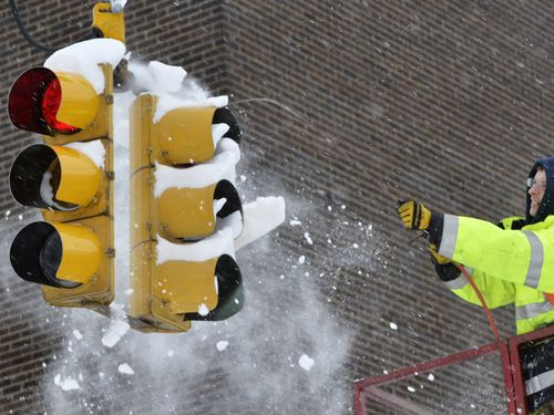 City of Erie traffic engineering employee Chuck Carnes Jr. uses compressed air to clear snow from a traffic signal. (AAP)