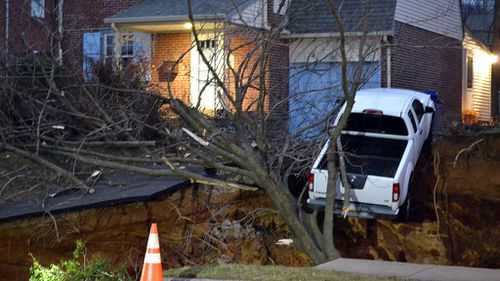 A giant sinkhole has swallowed up two front gardens in Philadelphia and a pick-up truck is teetering on the edge of the crater. (AAP)
