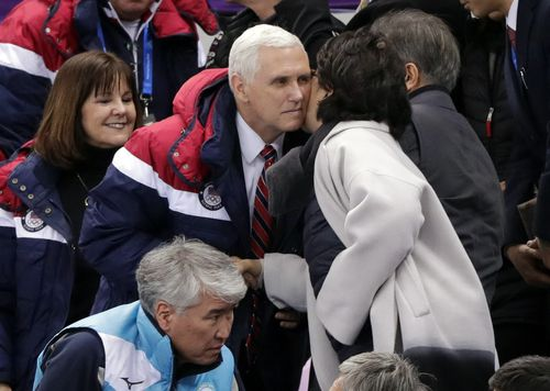 Mr Pence, center left, is greeted by an unidentified woman. (AP)