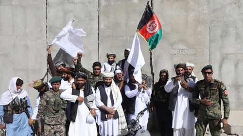 Afghan civilians carrying Afghan national flag along with Taliban flag stand with Taliban fighters and army soldiers. Picture: EPA
