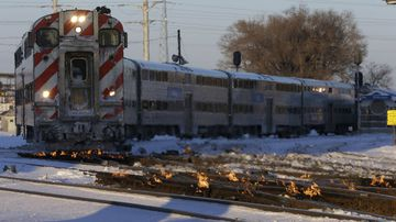 A Metra train moves southbound to downtown Chicago as the gas-fired switch heater on the rails keeps the ice and snow off the switches near Metra Western Avenue station in Chicago.