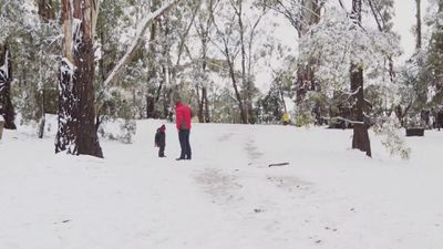 Family enjoys snow in Orange