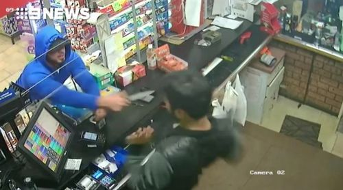 The thief lunges at the cashier after demanding cash.