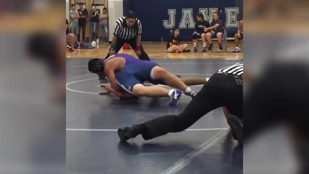 Wrestling ref slides across mat like an eel