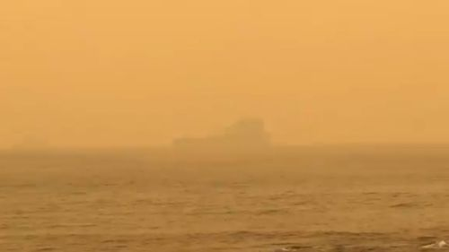 The HMAS Choules is barely visible from shore.
