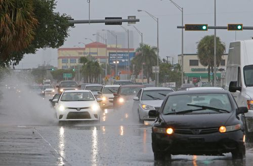 Cars push through a flooded street in Miami.