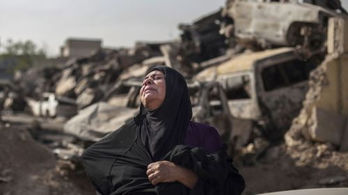 Fatima Ahmed Aswad cries as the body of her 15-year-old daughter Sana is exhumed in Mosul for forensic investigation in order to receive a death certificate. (AAP)