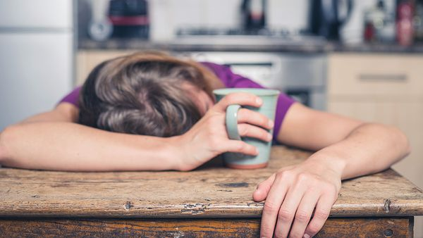 Person slumped on wooden desk holding a mug