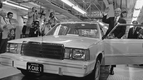 Lee Iacocca sits on the hood of K Car Number One, a Plymouth Reliant, in Detroit.