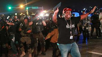 A citizen peacekeeper tries to keep protesters back as police advance in the suburb of St Louis, Missouri. (AP)