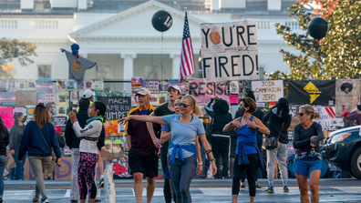 People gather on Black Lives Matter Plaza on the north side of the White House where a tall metal security fence has been covered in protest signs, early Sunday, Nov. 8, 2020. (AP Photo/J. Scott Applewhite)