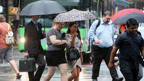 Pedestrians walk through the Brisbane CBD during rain. (AAP)