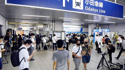 Police and journalists gather at Soshigaya Okura Station after the stabbing on a commuter train.