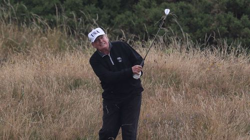 Donald Trump hits a shot during a game of golf.