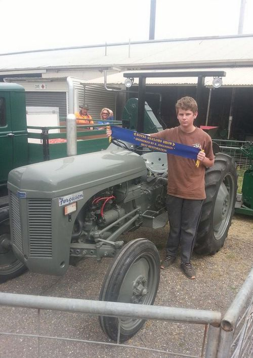 Sam with a prize-winning restored tractor on the farm. (Facebook)
