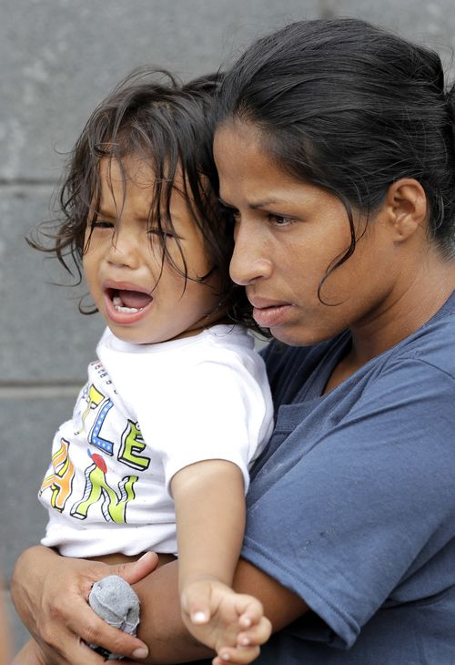 19-month-old Jesus Funes cries in the arms of his mother after the pair return across the Mexican border after being told by officials they'd be separated if they remained in the US. Picture: AAP