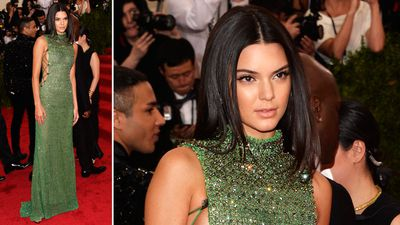 """Kendall Jenner knows how to keep up with the Kardashians, showing off """"side boob"""" in a beaded green Calvin Klein dress. (AAP)"""