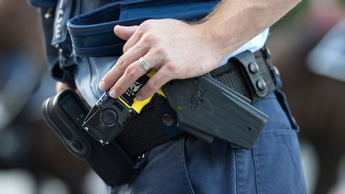A police officer rests a hand on a taser in the Brisbane CBD. (AAP)