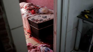 Blood covers the floor and a bed inside a home during a police operation targeting drug traffickers in the Jacarezinho favela of Rio de Janeiro, Brazil.