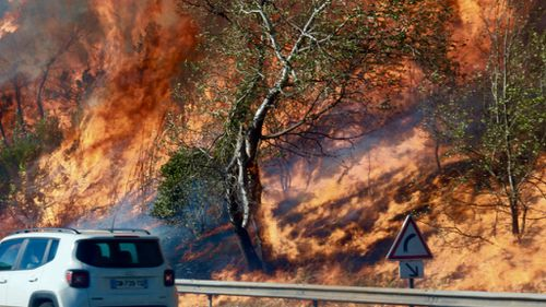 Fires burn on the side of the road in Vitrolles, north of Marseille. (AFP)