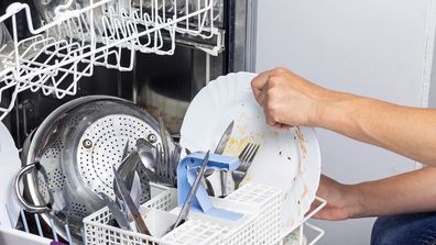 Woman putting dirty dishes in a dishwasher