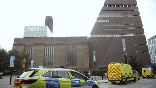"Emergency crews attending a scene at the Tate Modern art gallery, London, Sunday, Aug. 4, 2019. London police say a teenager was arrested after a child ""fell from height"" at the Tate Modern art gallery."
