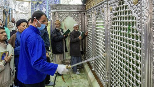 In this Monday, Feb. 24, 2020, photo, a man disinfects the shrine of Saint Masoumeh against coronavirus in the city of Qom 78 miles (125 kilometers) south of the capital Tehran, Iran