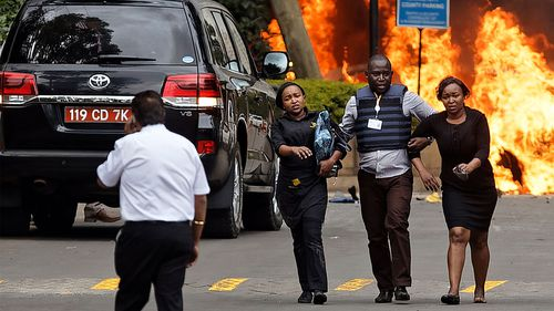 Bystanders are helped to ssfety as cars burn outside the DusitD2 hotel complex in Nairobi.