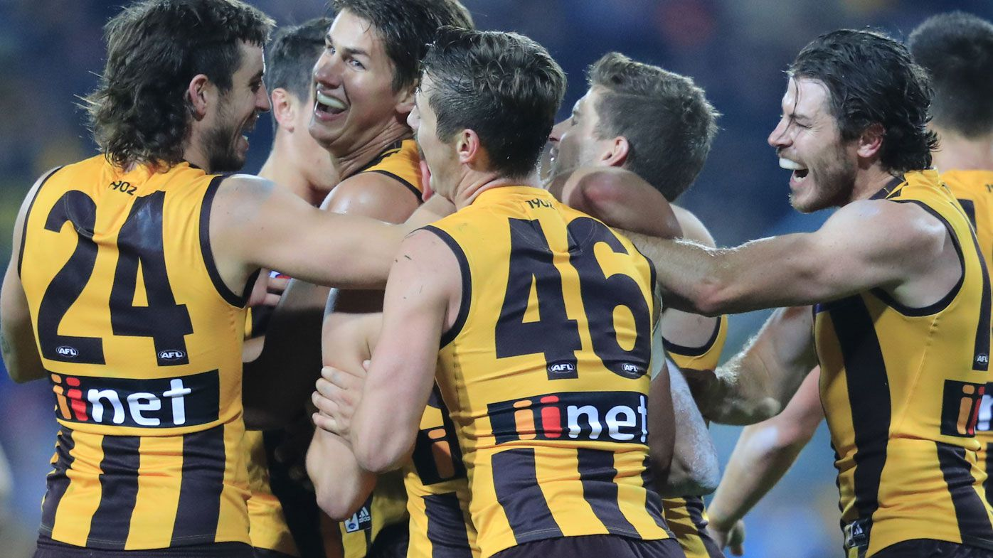 Hawks players celebrate a final quarter goal during the Round 6 clash at the University of Tasmania Stadium