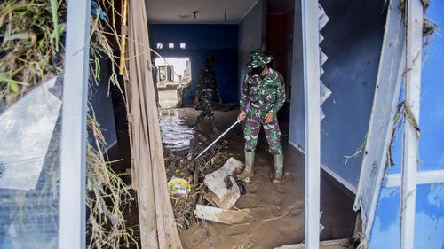 Indonesian soldiers examine the damage at a neighbourhood affected by a flood in Medan, North Sumatra, Indonesia, Friday, Dec. 4, 2020.