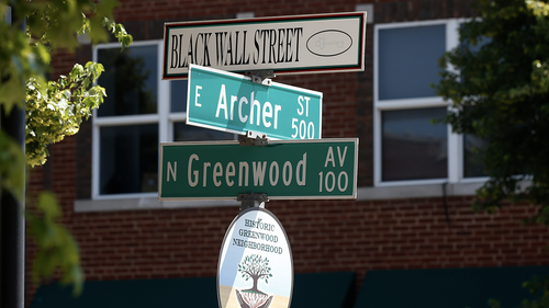 FILE - In this Monday, June 15, 2020, file photo, a sign marks the intersection of Greenwood Avenue and Archer Street, the former home of Black Wall Street, in Tulsa, Okla. Black community leaders in Tulsa said they fear a large rally by President Donald Trump in the city this weekend could spark violence, and the state's governor asked Trump not to visit the site of a race massacre where up to 300 black residents were killed by white mobs in 1921. (AP Photo/Sue Ogrocki)