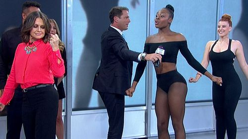 Lisa gives J-Lo's moves a try while Karl is preoccupied holding a mic for demo dancer Ebony. (9NEWS)