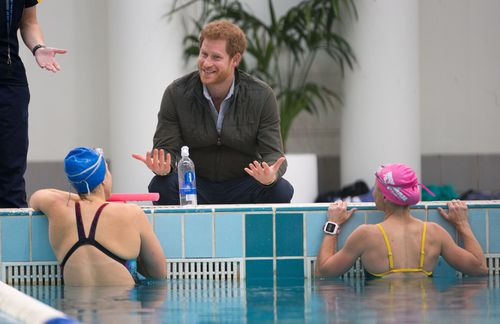 Prince Harry speaks to members of the Australian Invictus swimming squad during a visit to the Aquatic Centre at the Olympic Park Sports Centre in Sydney. (AAP)