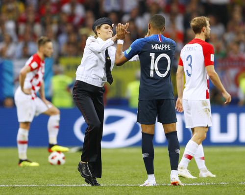 An intruder (L) high-fives Kylian Mbappe of France during the second half of the World Cup final between France and Croatia at Luzhniki Stadium in Moscow on July 15, 2018. Russian protest group and musical act Pussy Riot has claimed responsibility for the incident. (Kyodo via AP Images)