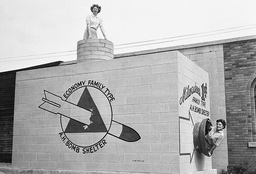 Beverly Wysocki, top, and Marie Graskamp, right, emerge from a new bomb shelter on display in the US in 1958. (AAP)
