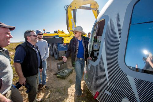 Jeff Bezos, centre, and others inspect Crew Capsule 2.0 after a test flight touchdown in West Texas.