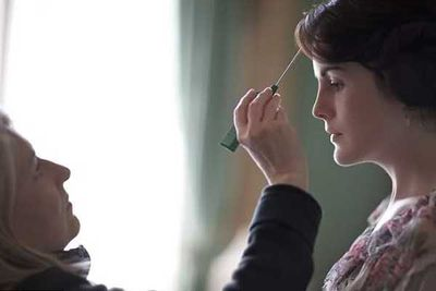 A stylist tends to stray hairs on Michelle Dockery (Lady Mary Crawley).