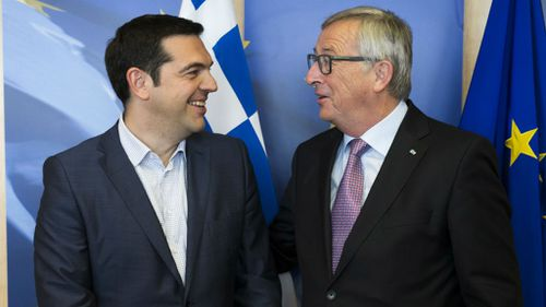 Greek Prime Minister Alexis Tsipras, left, is greeted by European Commission President Jean-Claude Juncker. (AAP)