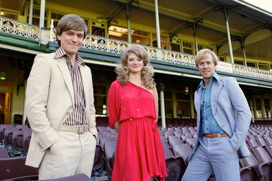 """Actors appearing in the TV production titled """"Howzat!"""" during the final days filming at the SCG. From left is Abe Forsythe (John Cornell), Cariba Heine (Delvene Delaney) and Travis Mcmahon (Paul Hogan) 23rd May 2012 Photograph by Dallas Kilponen"""