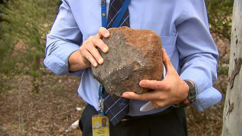 Police show one of the rocks believed to have been thrown in the incident.