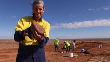 Robyn Mackenzie, Director and palaeontologist for the Eromanga Natural History Museum, holds up a dinosaur bone.