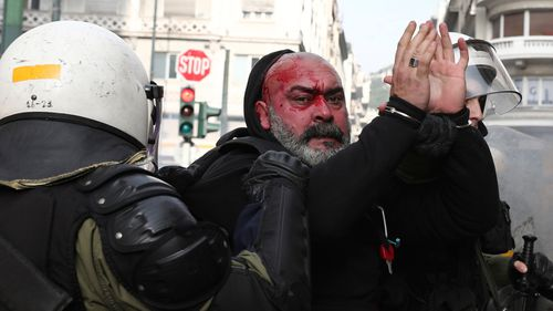 Riot policemen detain a protester during a scuffle on the sidelines of a rally in Athens. (AP)