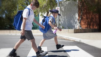 School children crossing the road safely at the cross walk.