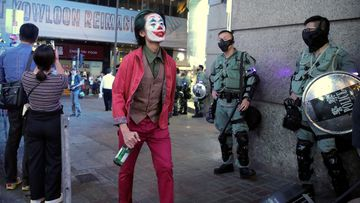 A man in a Halloween costume walks past police officers in riot gear in Hong Kong.