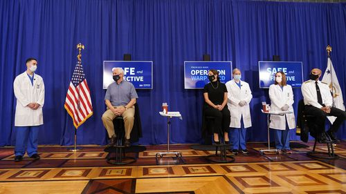 Vice President Mike Pence, seated left, his wife Karen Pence, seated center, and U.S. Surgeon General Jerome Adams, seated right prepare to receive a Pfizer-BioNTech COVID-19 vaccine shot at the Eisenhower Executive Office Building on the White House complex, Friday, Dec. 18, 2020, in Washington