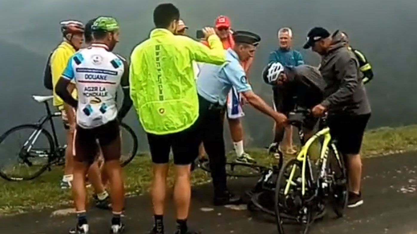 Police force Chris Froome off his bike during 17th stage of Tour de France
