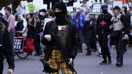 A woman carries a gun during a march in support of vote counting after the Nov. 3 elections, Wednesday, Nov. 4, 2020, in Portland, Ore