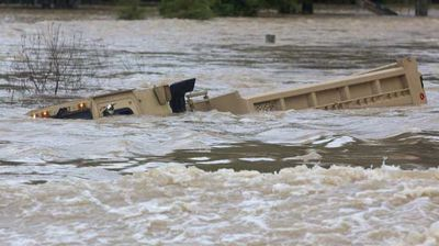 A Louisiana Army National Guard dump truck that drove off the road is submerged in flood waters. (AP)