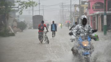 Haitian people travel in a flooded street through the rain during a tropical storm in the commune of Les Cayes, Haiti, on October 21, 2016. (AFP)
